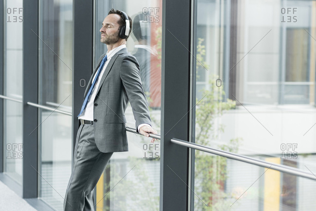 Portrait of businessman with eyes closed listening music with headphones