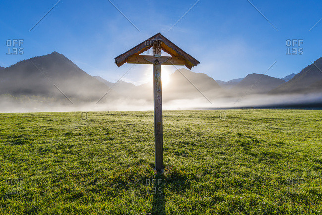 October 5, 2018: Germany- Bavaria- Allgaeu- Allgaeu Alps- Loretto meadow near Oberstdorf- field cross against morning sun