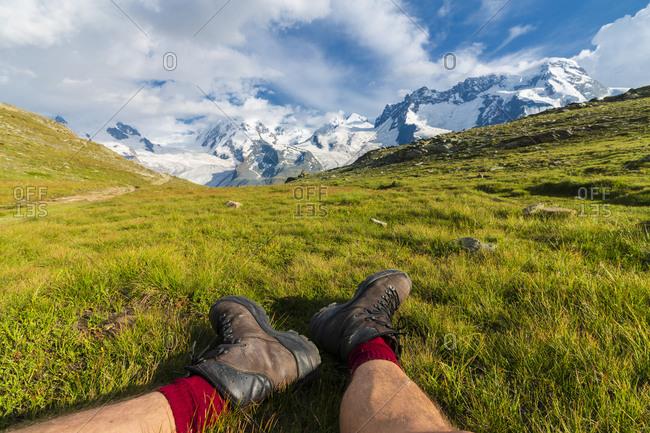 Hiker rests on grass looking towards Monte Rosa massif, Riffelalp, Zermatt, canton of Valais, Swiss Alps, Switzerland, Europe