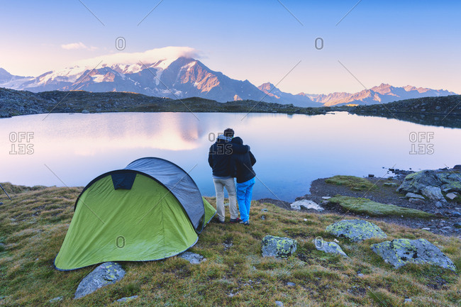 A couple admires the sunrise at the lake of Manzina, Valfurava, Valtellina, Italy, Europe