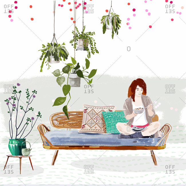 Everyday ordinary setting of a woman eating on the couch in a home environment