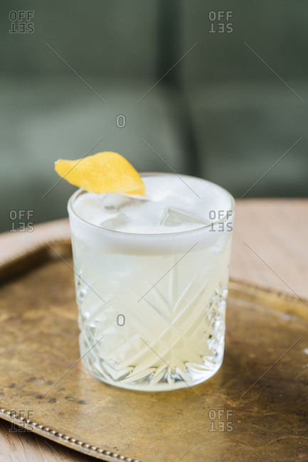 Fresh lemon cocktail on a golden serving tray