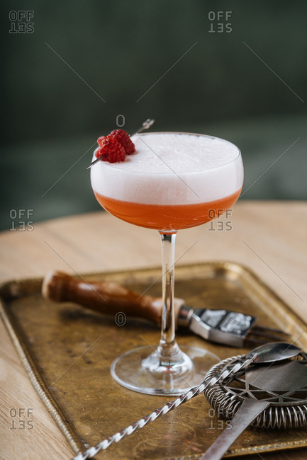 Pink cocktail garnished with a raspberry on a bar table with cocktail tools