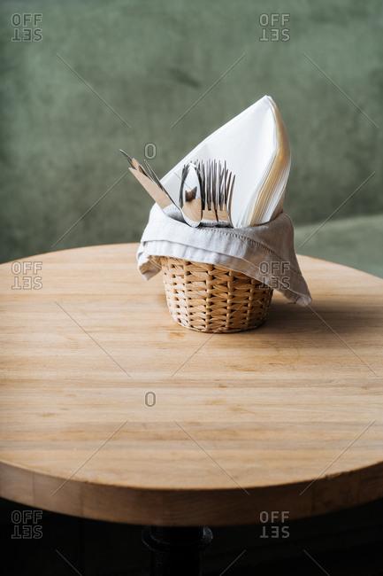 Basket of utensils on a sage green background