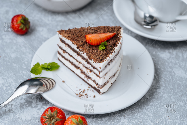Layered cake with chocolate shavings and strawberry on top