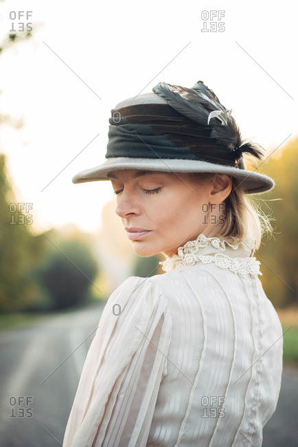 Woman dressed in vintage dress and hat with her eyes closed