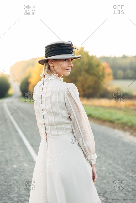 Woman in vintage dress and hat standing on country road looking back