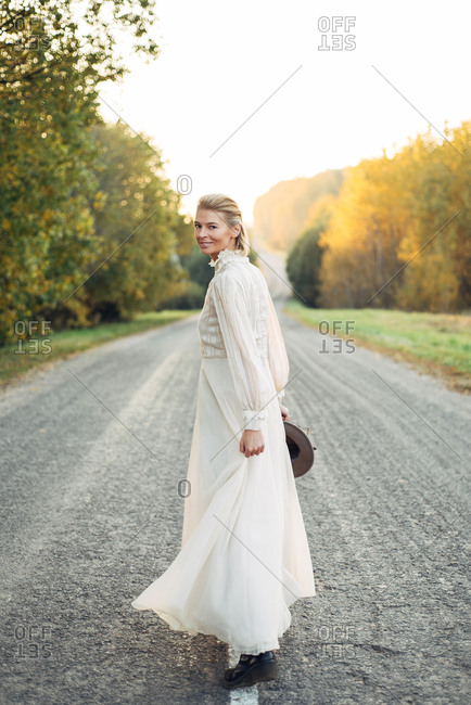 Smiling woman in vintage dress looking back on country road