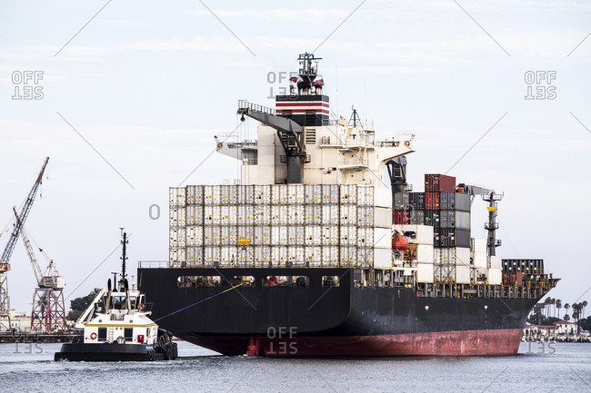 Los Angeles, California, USA - July 18, 2018: Tugboat pulling a large container ship out to sea from metropolitan port