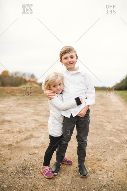 Two blonde siblings hugging
