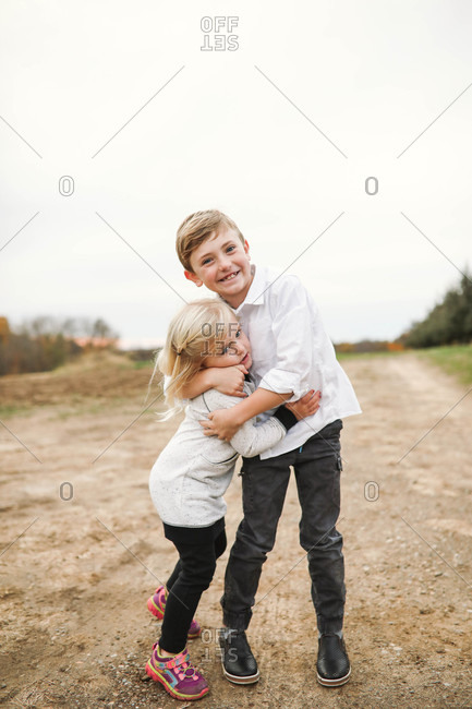 Two siblings hugging outdoors - Offset