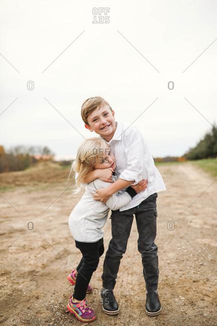 Two siblings hugging outdoors