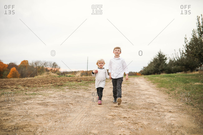 Two blonde siblings walking hand in hand
