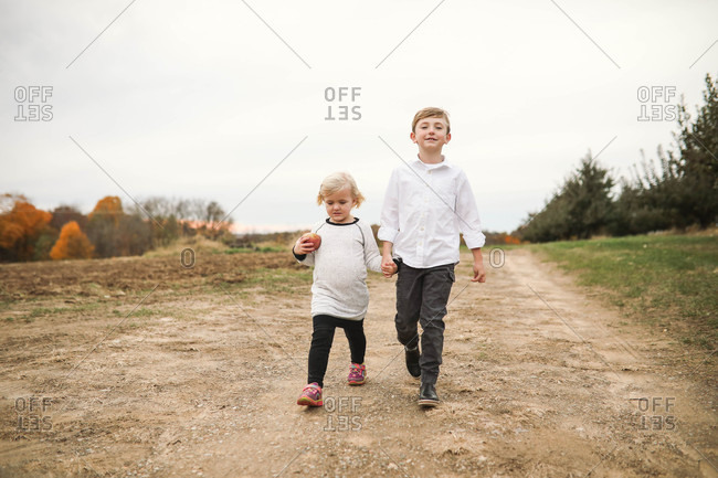 Two blonde siblings walking and holding hands