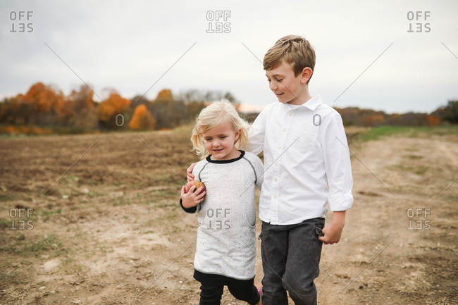 Siblings walking with arms around each other