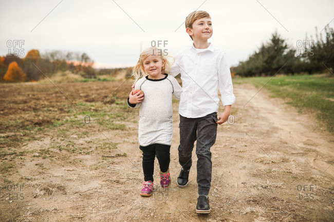 Two siblings walking with arms around each other