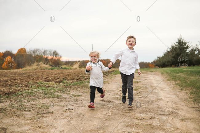 Siblings running hand in hand