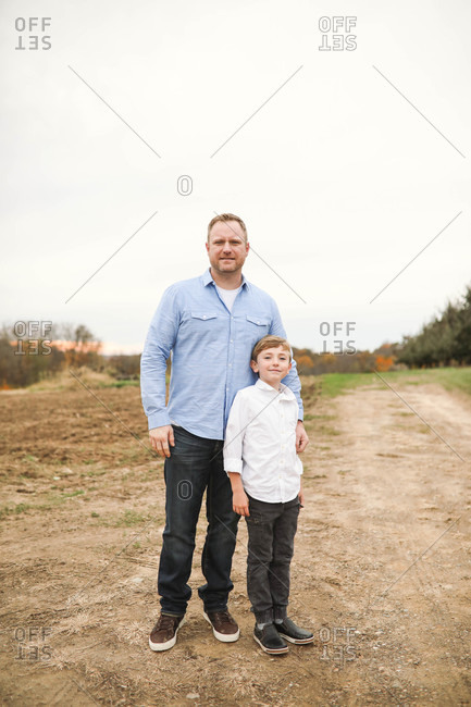 Father and son standing in country together