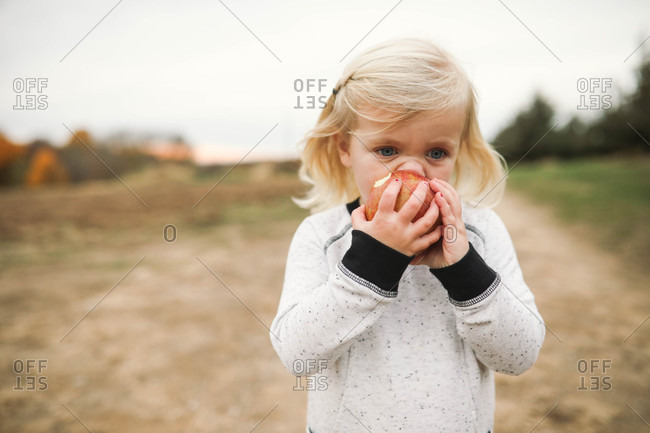 Young blonde girl eating an apple