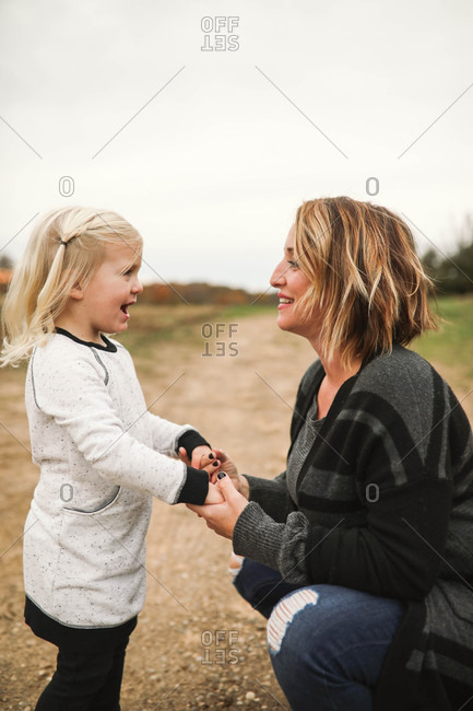 Mother and daughter holding hands face to face