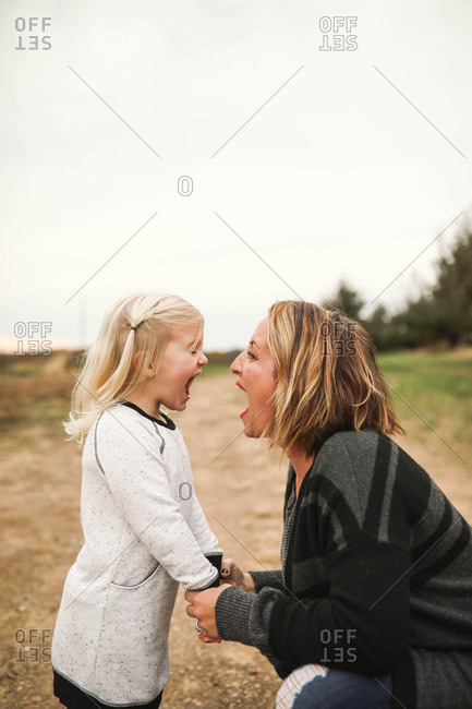 Mother and daughter holding hands making silly faces