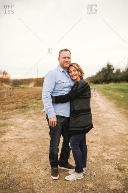 Husband and wife hugging in countryside