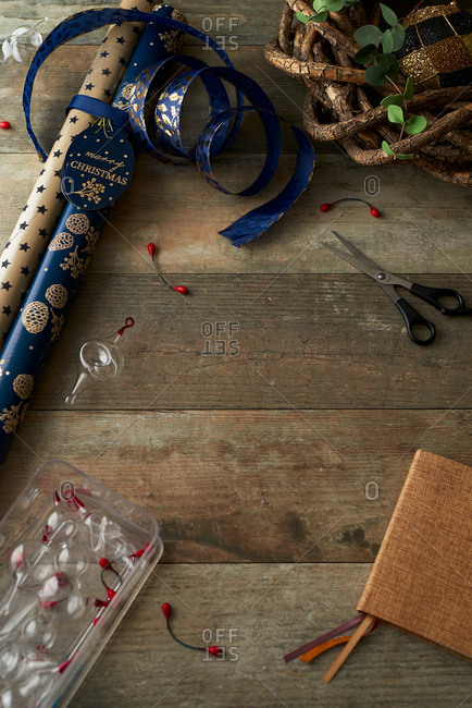 Christmas wrapping paper and ornaments on wooden table