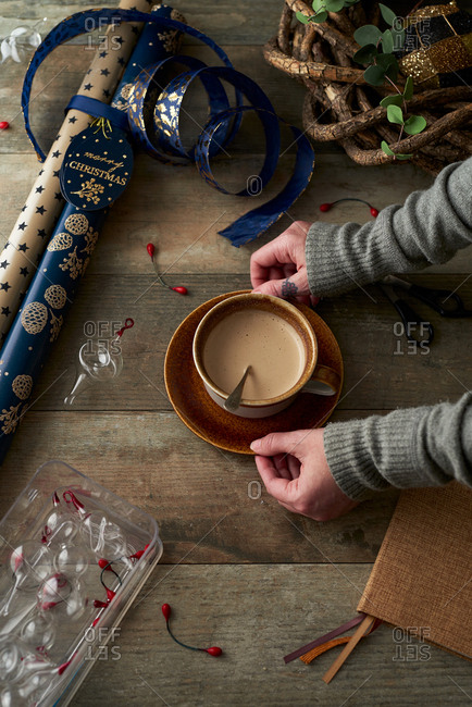 Woman placing cocoa beside Christmas wrapping paper on wooden table