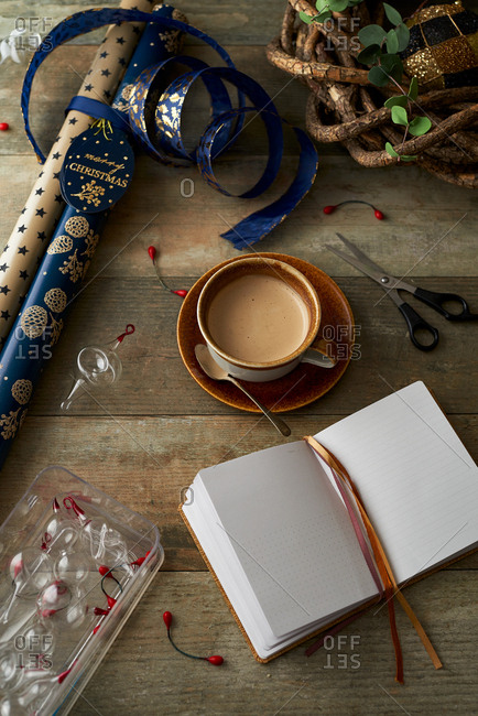 Open journal beside Christmas wrapping paper and cocoa