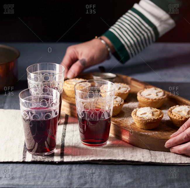 Woman serving mince pies and mulled wine