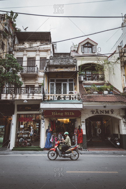 Hanoi, Vietnam - October 14, 2018: Person riding a motorcycle on the street through business district