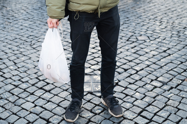 Close up of a man holding a plastic bag