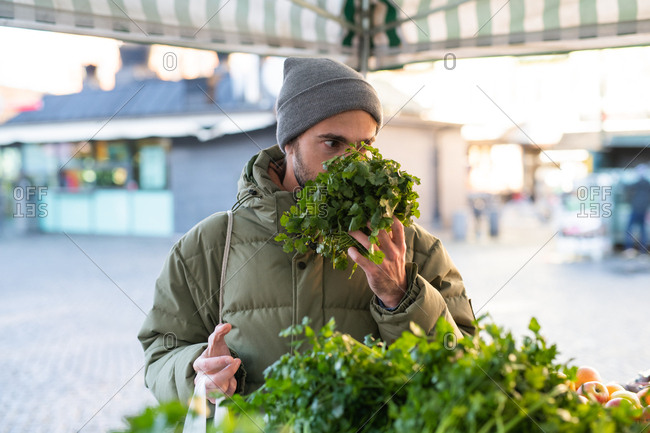 Man smelling a bunch of fresh cilantro at farmers market