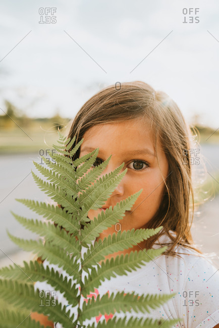 Girl holding fern in front of her face