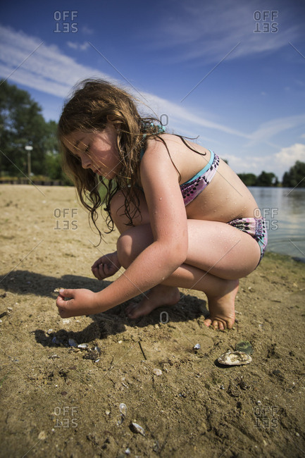 Girl in her swimsuit picking up seashells along the sandy shore of a lake