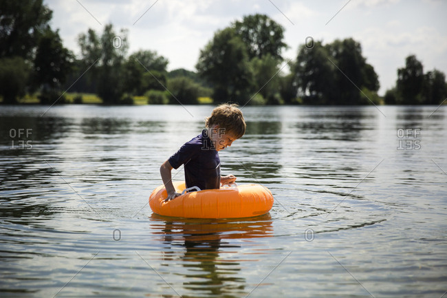 Boy using inflatable swim ring in the water of a lake