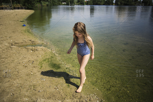 Girl wading in the water along the sandy shore of a lake