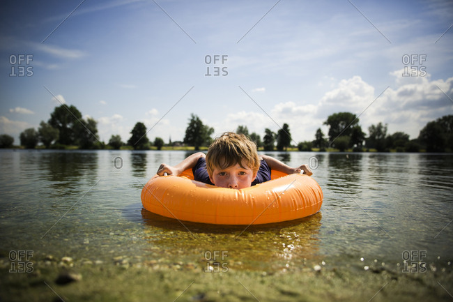 Boy floating on an inflatable swim ring in shallow water along the shore of a lake