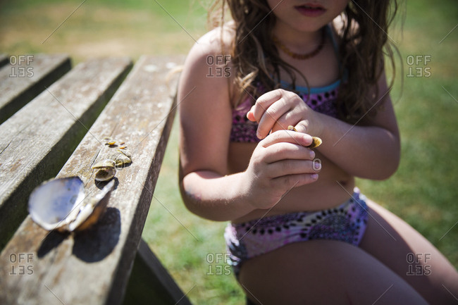 Girl sitting at wooden table with seashells