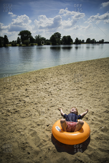 Boy lying on an inflatable swim ring along the sandy shore of a lake