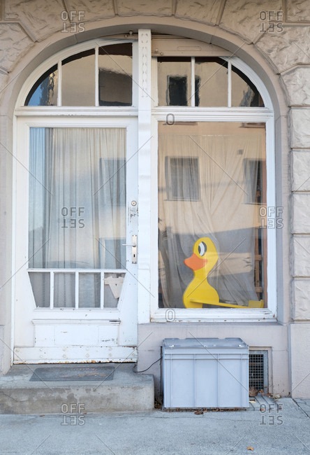 Yellow duck seen through window