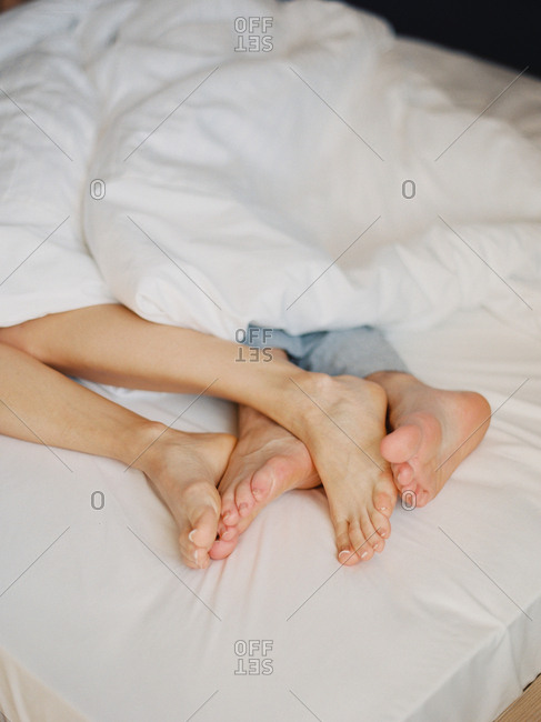 Feet of couple cuddling in bed together
