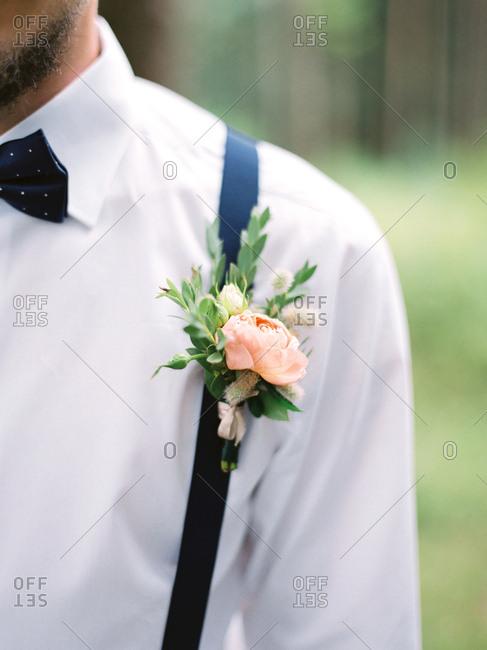Groom wearing boutonniere on suspenders