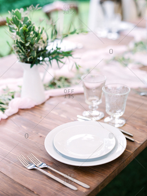 Place setting on a wooden table at an outdoor wedding