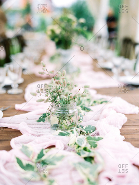 Thistle floral arrangement on a table at an outdoor wedding