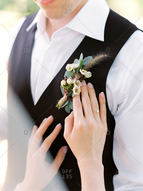 Bride touching groom's boutonniere