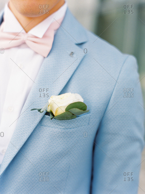 Groom wearing light blue suit and boutonniere
