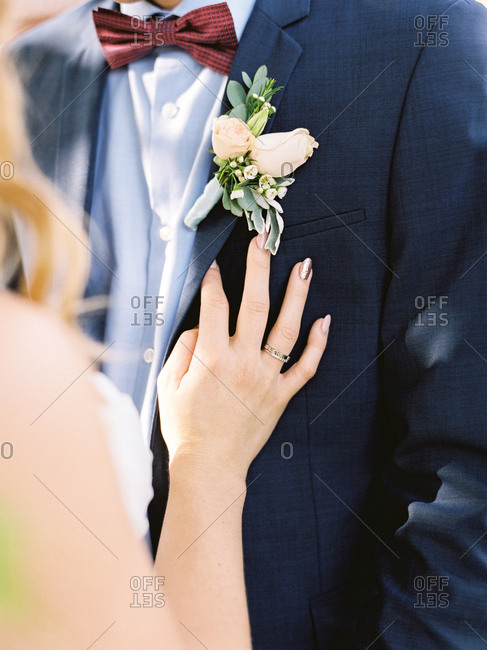 Bride touching groom's chest by boutonniere