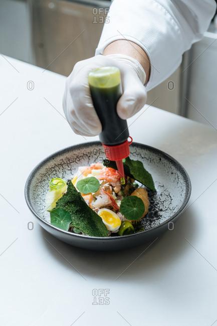 Chef preparing dish with sauce