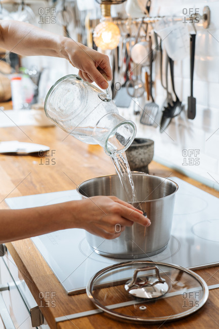 Woman pouring water into pot on stove